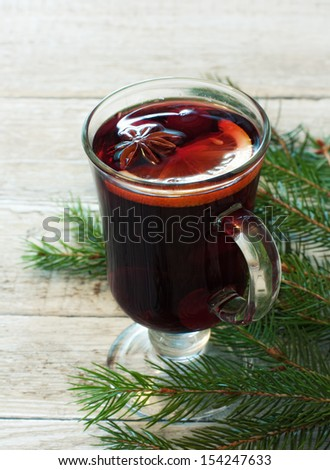 Glass of mulled wine and fir over wood background