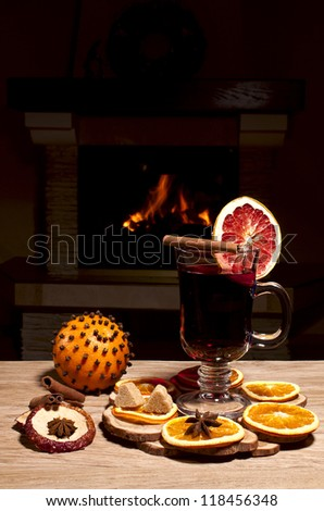 glass of mulled wine on the background of a burning fireplace - stock photo