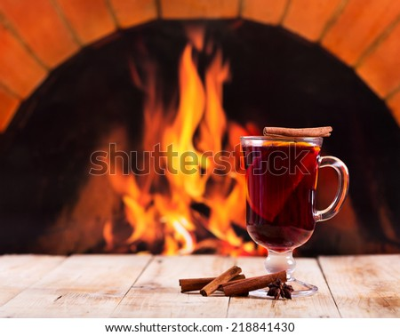 glass of mulled wine on wooden table over fireplace - stock photo