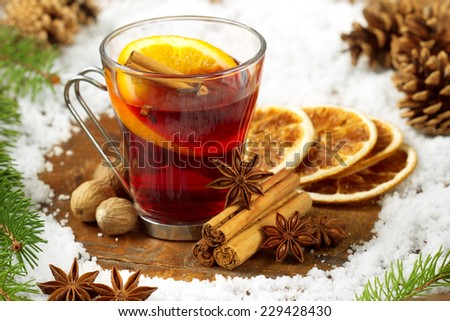 glass of mulled wine, spices and snow on wooden table - stock photo