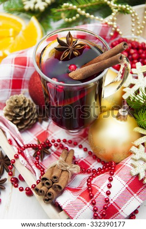 Glass of mulled wine with spices and Christmas decoration on a wooden background