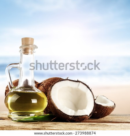 glass of oil and coconuts  - stock photo