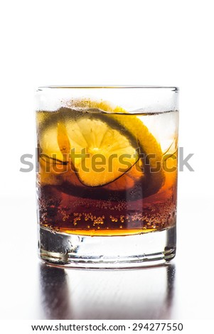 Glass of old fashioned cocktail with cola, ice and lemon slice - stock photo