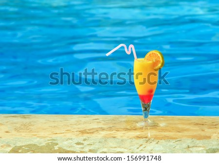 Glass of orage juice is on edge of pool - stock photo