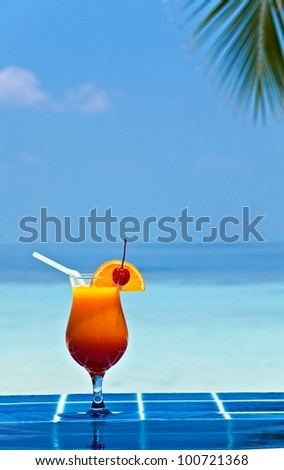 Glass of orage juice is on edge of pool made from glazed tile  in tropical hotel, Maldives - stock photo