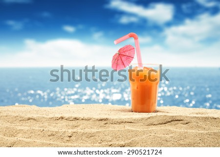 glass of orange juice and sand  - stock photo