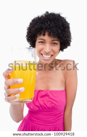 Glass of orange juice being held by a young female who is smiling - stock photo
