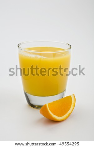 Glass of orange juice isolated on white with orange wedge in foreground - stock photo