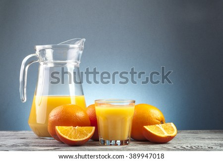 Glass of orange juice, jug and ripe oranges on wooden table - stock photo