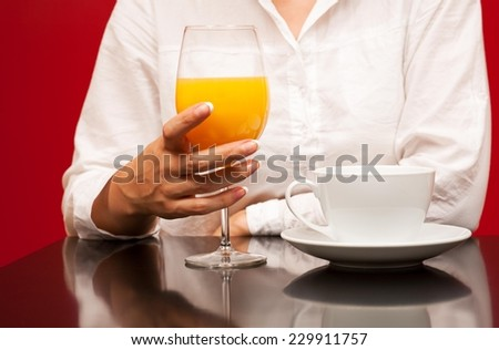 Glass of orange juice on the red table and female holding cup of coffee - red background