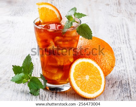 Glass of orange juice on wooden table, on wood plants background, fresh drink - stock photo