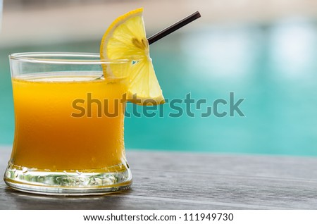 Glass of orange juice with orange slice with pool background - stock photo
