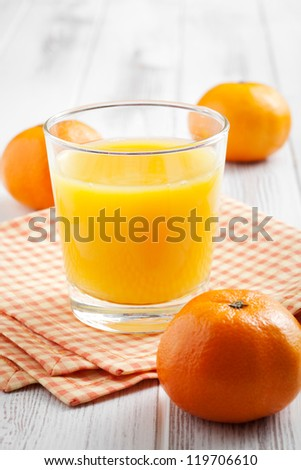 Glass of orange juice with some tangerines - stock photo