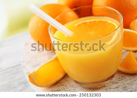 Glass of orange juice with straw and slices on wooden table background