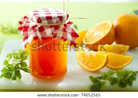 glass of orange marmelade with orange slices - stock photo