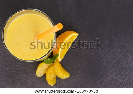 Glass of orange smoothie, isolated on slate plate. Top view. - stock photo