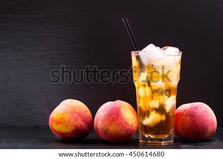 glass of peach iced tea with fresh fruit on dark background