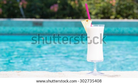 Glass of Pina Colada cocktail on the pool nosing at the tropical resort. Horizontal, wide screen, cocktail on right side - stock photo