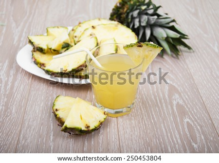 Glass of pineapple juice with fresh fruits on a wooden background - stock photo