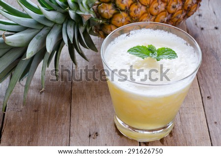 Glass of pineapple smoothie with fresh mint leaves and pineapple on wooden table - stock photo