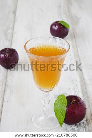 glass of plum juice and ripe plums on a light background.selective focus.health and diet food