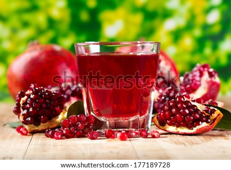 glass of pomegranate  juice with fresh fruits on wooden table - stock photo