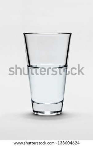 Glass of pure water on light gray background. The glass is half-full or half-empty. - stock photo