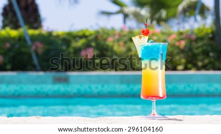 Glass of Rainbow cocktail on the pool nosing at the tropical resort. Horizontal, wide screen, cocktail on right side - stock photo