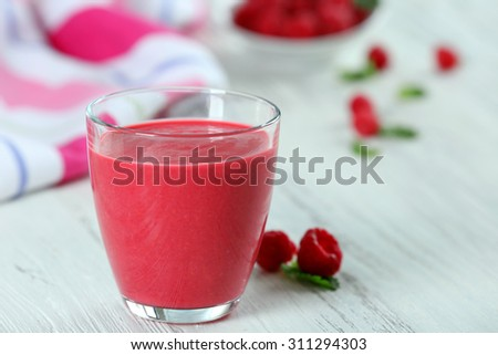 Glass of raspberry milk shake with berries on wooden table close up