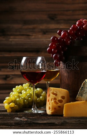 Glass of red and white wine, cheeses and grapes on brown wooden background