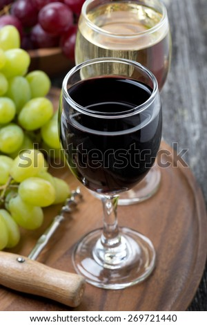 glass of red and white wine, corkscrew and grapes on a wooden board, top view - stock photo