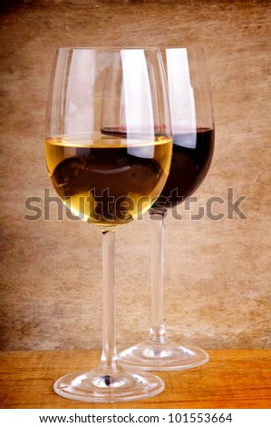 glass of red and white wine on a vintage wooden background