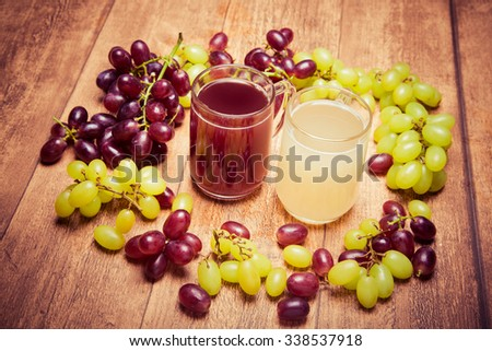 Glass of red stum and 2 glasses of white stum together with some green and red grapes photographed on a piece of wood in retro style. - stock photo