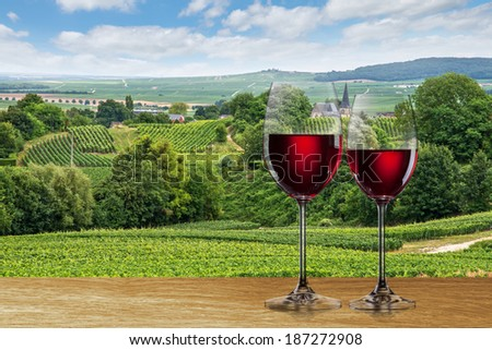 Glass of red wine against vineyard landscape - stock photo
