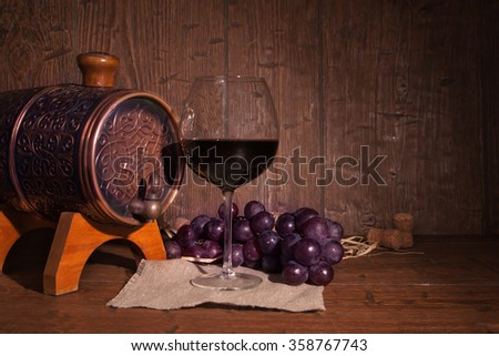 Glass of red wine and barrel on rustic wood tabel.