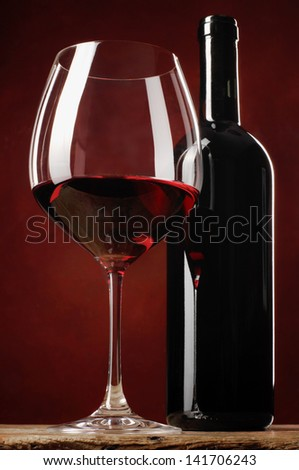 Glass of red wine and bottle on a table