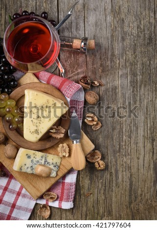 Glass of red wine and cheese on rustic wooden background