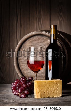 Glass of red wine and cheese with a bottle on the background of wooden wall