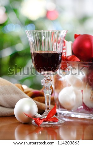 Glass of red wine and Christmas decorations in front of Christmas tree for the holidays
