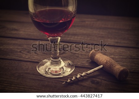 Glass of red wine and corkscrew on an old wooden table. Angle view, image vignetting and the yellow toning
