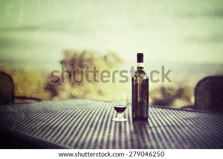 Glass of red wine and empty bottle on the table at morning time early fall. Tuscan, Italy. Filtered image. Vintage effect applied - stock photo