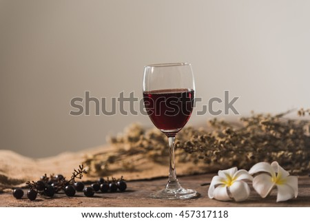 Glass of red wine and grapes - stock photo