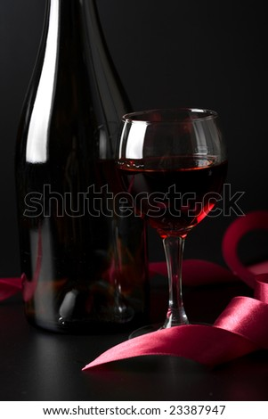 glass of red wine and red ribbon over black background
