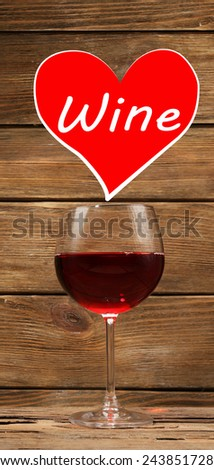 Glass of red wine and sample text in heart on wooden background - stock photo