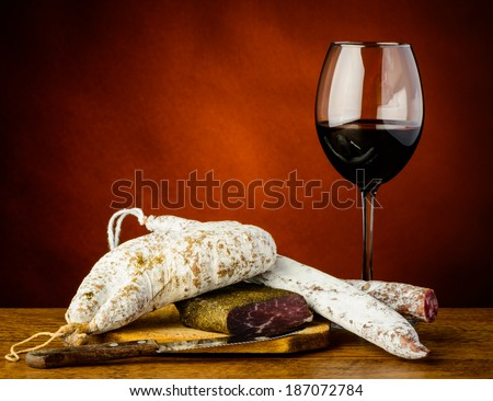 glass of red wine and traditional sausages on a wooden plate