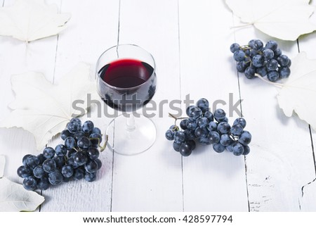 glass of red wine, blue grapes and leaves on white wooden table background