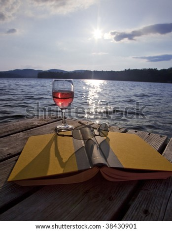 Glass of red wine, book, and sunglasses on a dock at a lake
