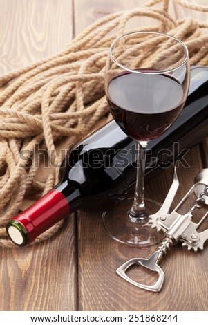 Glass of red wine, bottle and corkscrew on rustic wooden table - stock photo