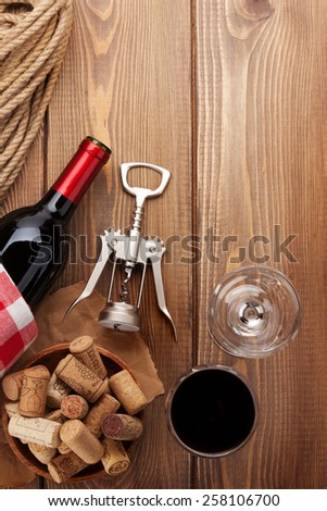 Glass of red wine, bottle and corkscrew on rustic wooden table. Top view with copy space - stock photo