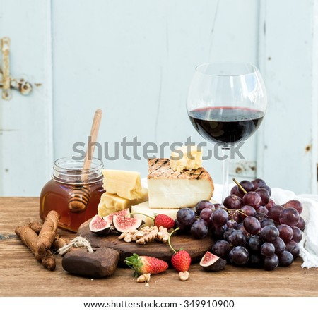 Glass of red wine, cheese board, grapes,fig, strawberries, honey and bread sticks  on rustic wooden table, blue background, selective focus - stock photo
